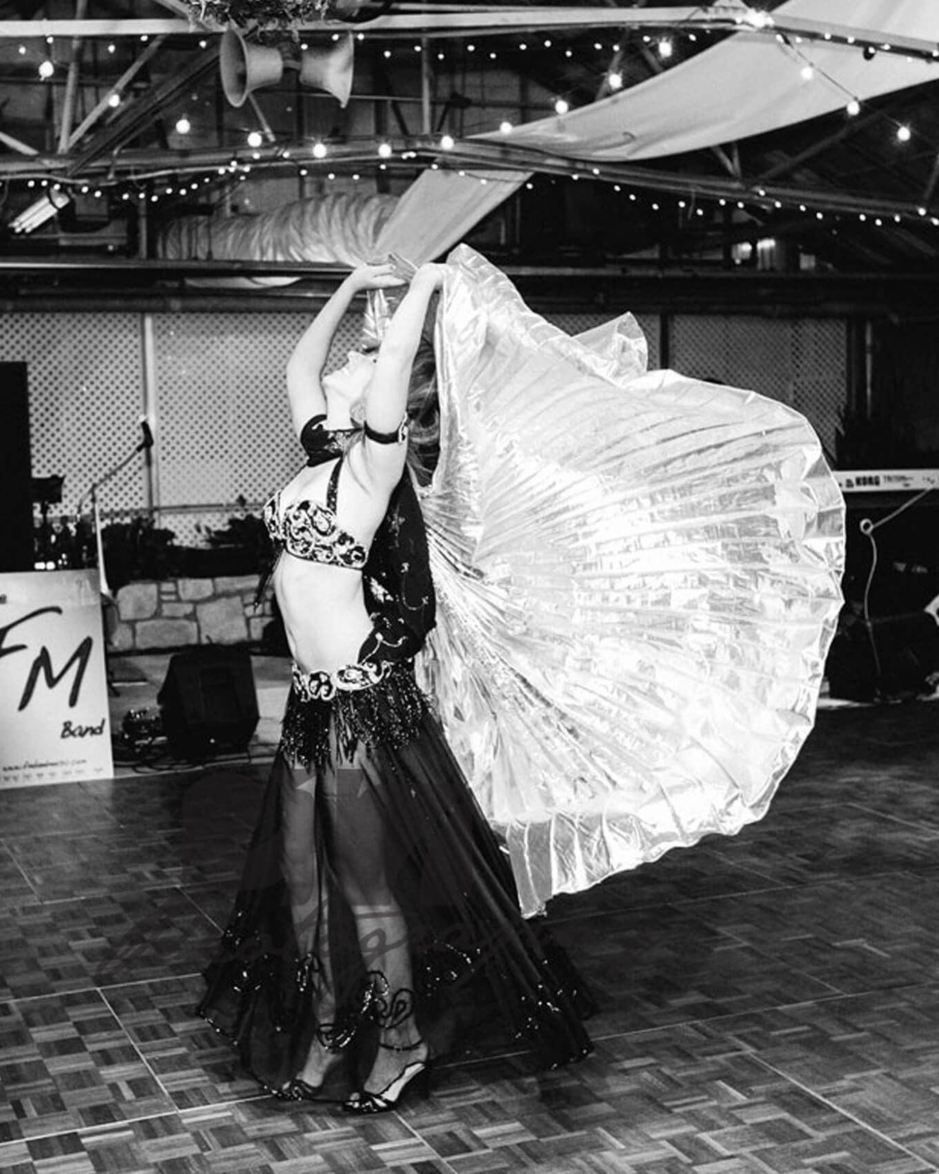 Donna performs using her belly dancing outfit with isis wings