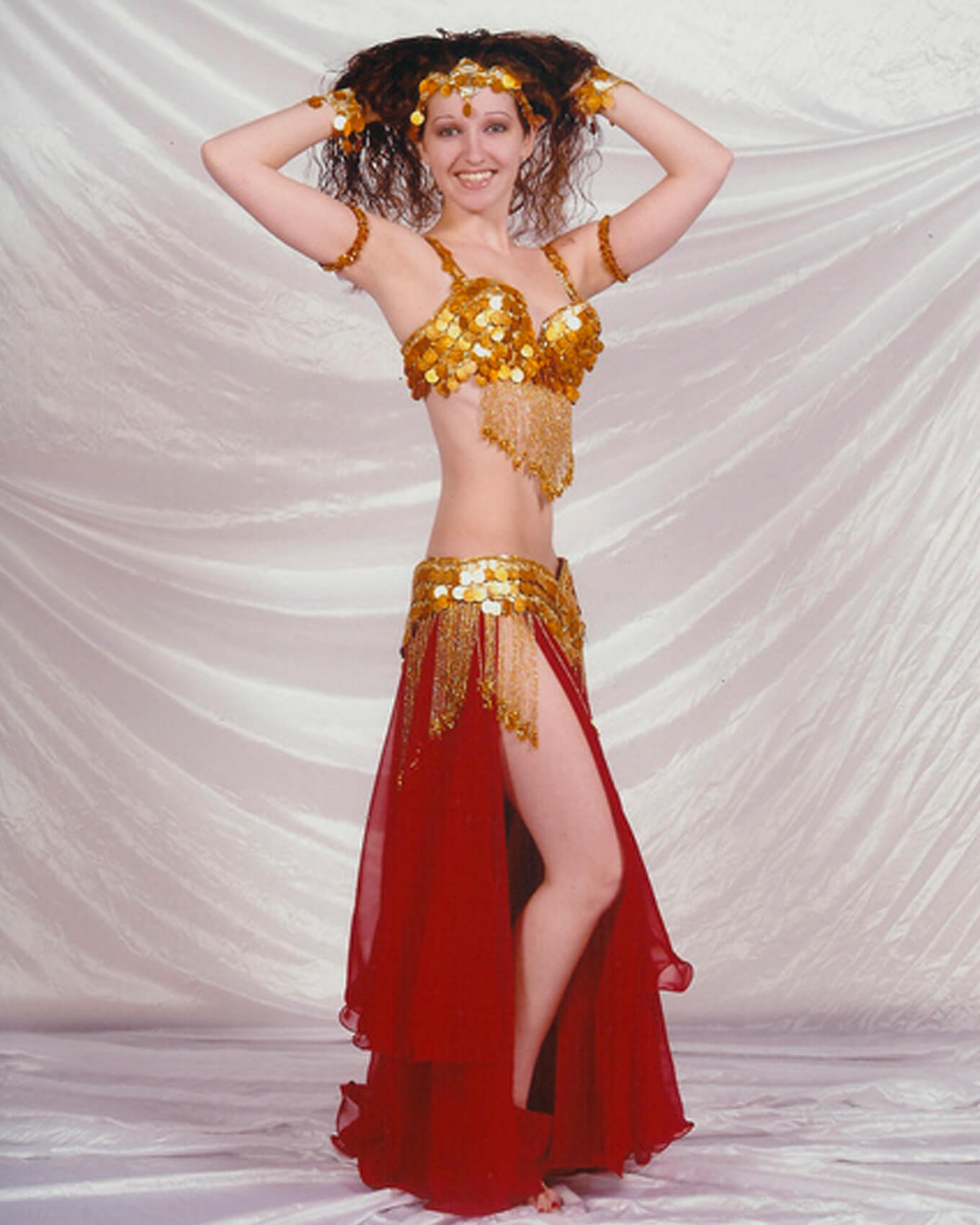 Donna wearing one of her red and gold belly dance outfits